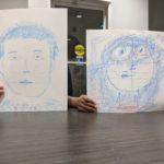 Two kids holding portraits over their faces