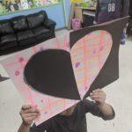 Child holds up heart artwork