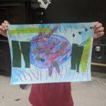 Child holds up rainbow fish art